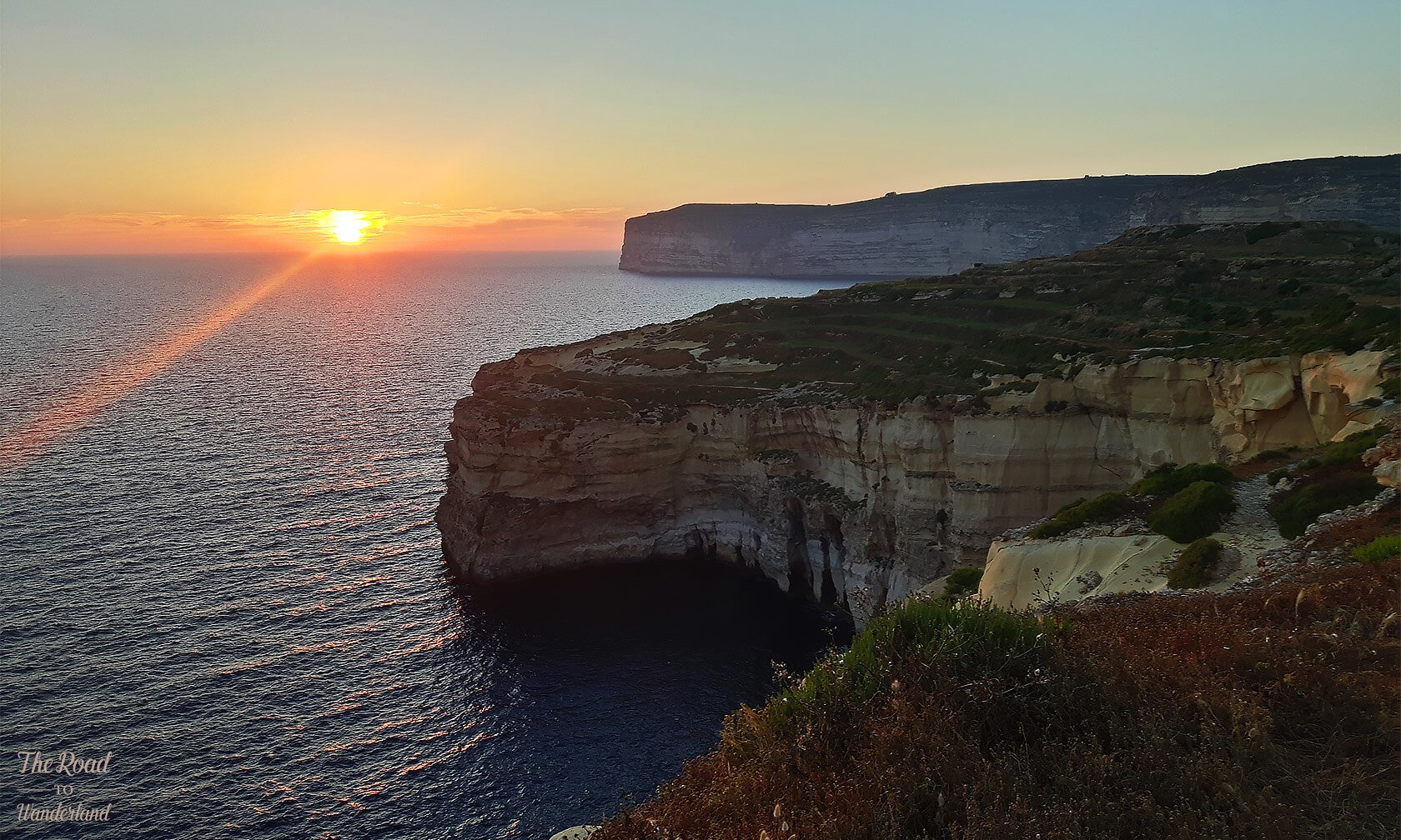 The sun setting beyond Xlendi cliffs