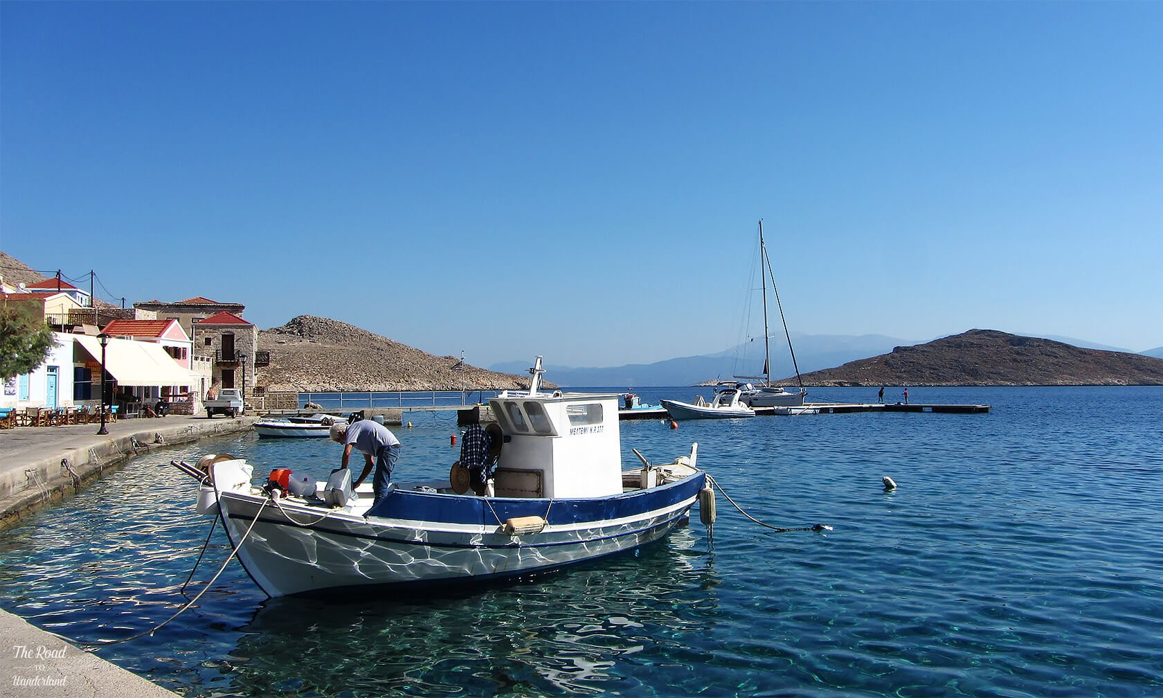 Fisherman pottering on his boat in Halki harbour